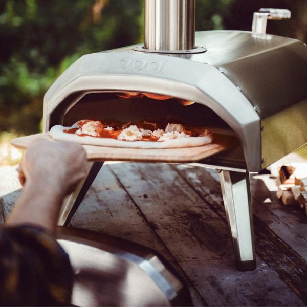 Hombre sacando una pizza de un horno ooni