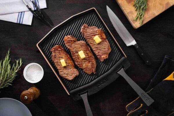 tres carnes sobre una parrilla de metal con un cuchillo al lado